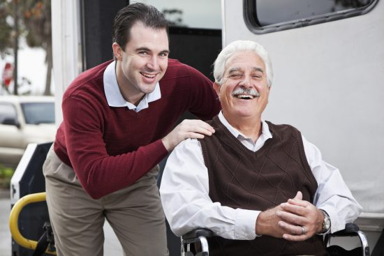 Senior man by disabled man with wheelchair lift